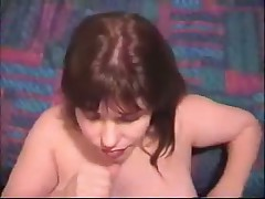 Mature wife strokes man's penis, seizing it with her hands and takes plentiful cumshot on her face.