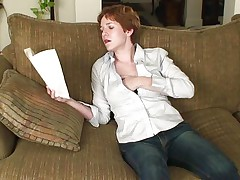 Sexy redhead Gigi is sitting on her couch, reading a book. Something in that book made Gigi horny and she starts to slowly touch herself. Before she knows it the naughty mature is topless and has her hand under those blue jeans, rubbing her cunt with desire. Keep on reading Gigi and we will keep on watching you!